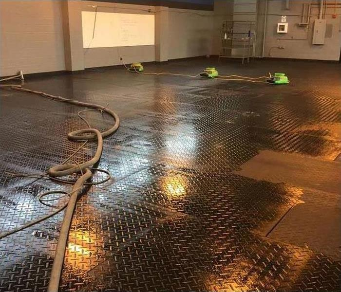 wet mats on a gym floor with a fire house across it and SERVPRO air movers on floor
