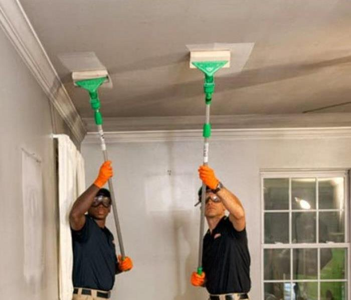 2 SERVPRO techs cleaning the ceiling