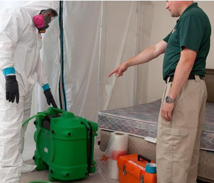 SERVPRO tech dressed in full protection suit, a manager pointing to big green bucket and a bed in the background