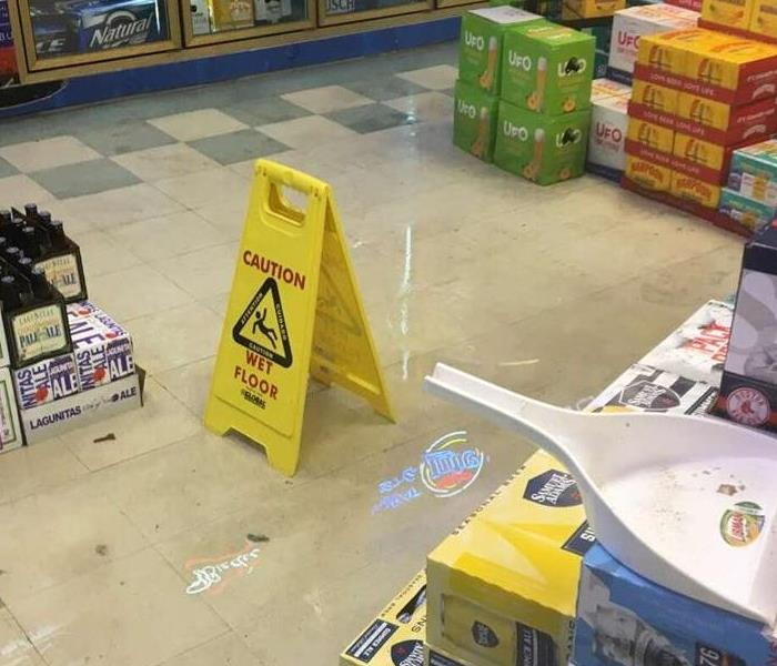 Wet floor sign in standing water on floor in liquor store with cases of beer surrounding water
