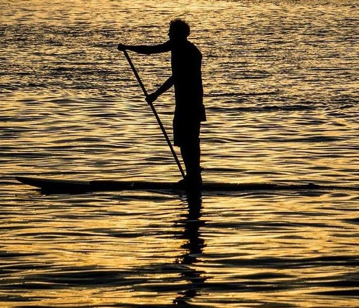 man on a paddle board paddling across a calm lake as the sun goes down