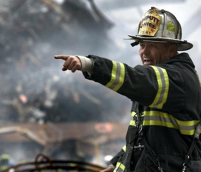 fireman pointing to the left in front of a background filled with large debris
