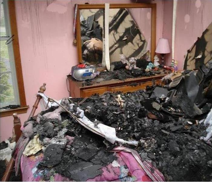 fire damage and debris in a bedroom